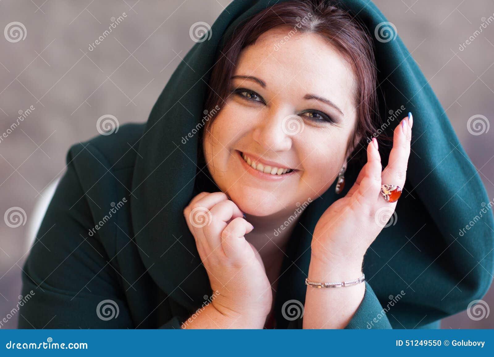 Las sonrisas preciosas de la mujer atractiva gorda