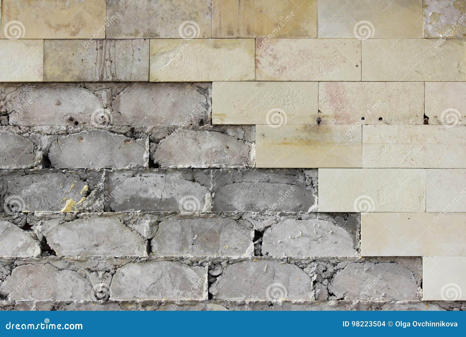 Las tejas beige grandes de la pared se cayeron, la textura de la fundación concreta Trabajo defectuoso