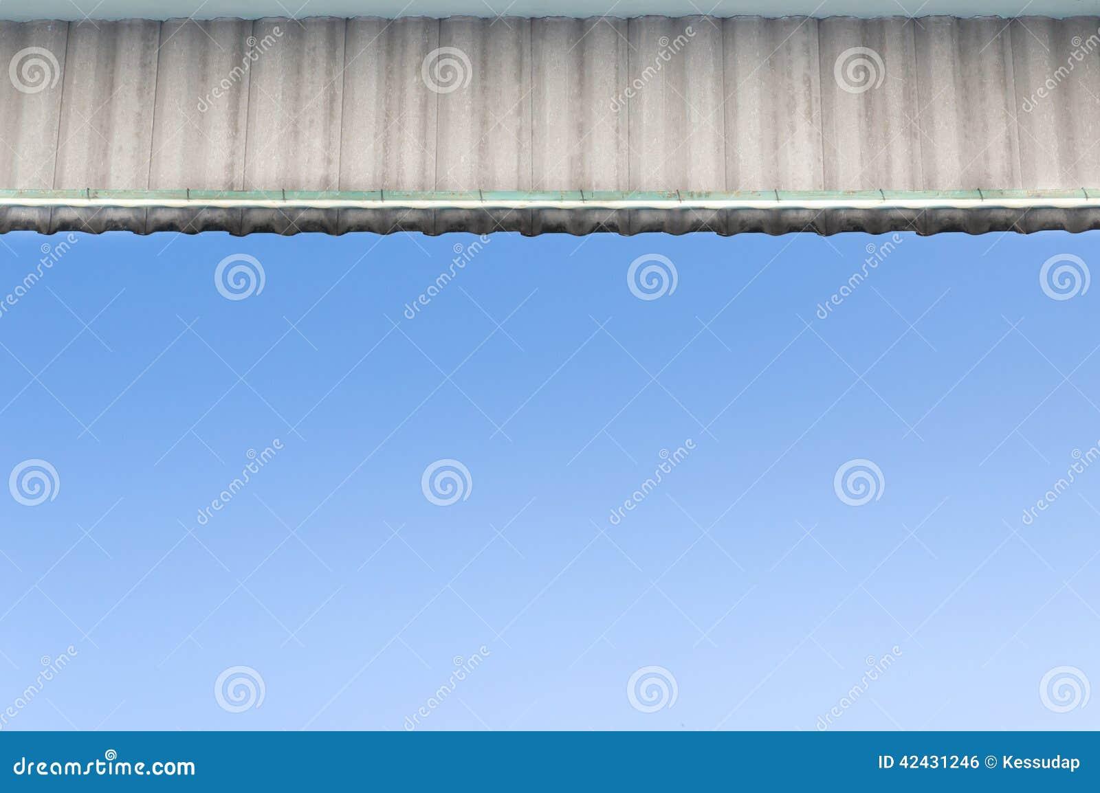 Las tejas de tejado con el fondo azul de la visión inferior