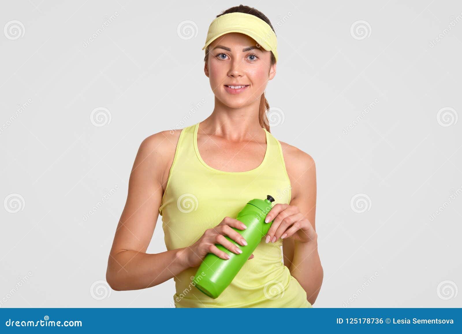 Las tomas activas hermosas sedientas de la mujer se rompen después de jugar al tenis, vestido en ropa de deportes casual, botella