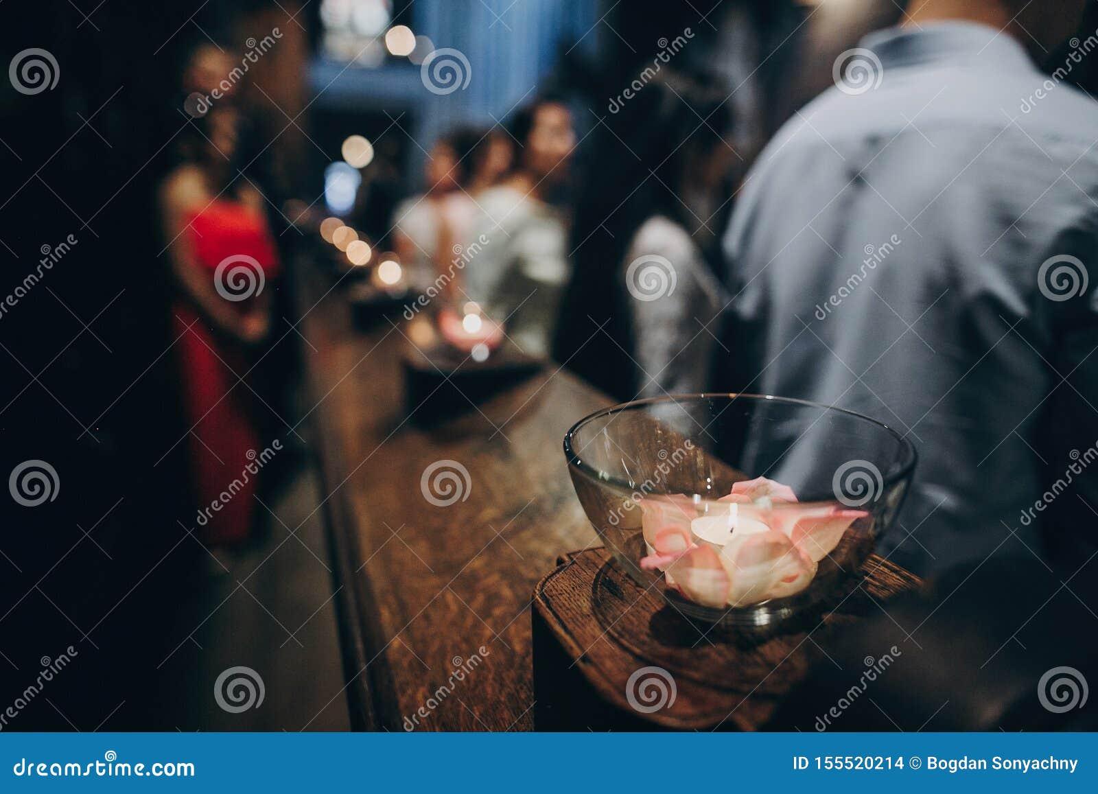 Las velas se encienden en vidrio en el altar de madera o banco en iglesia en el matrimonio santo Festival de Diwali de la luz Que