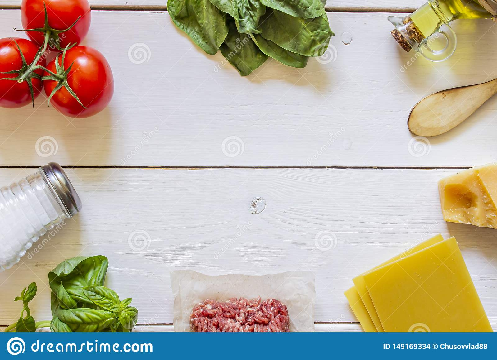 Lasa?as, tomates, carne picadita y otros ingredientes Fondo de madera blanco Cocina italiana