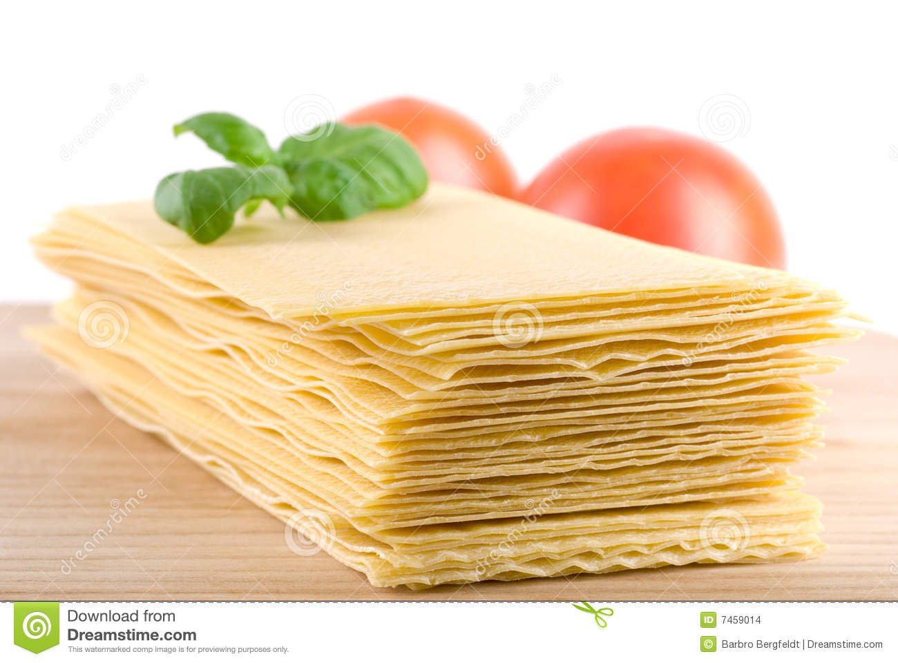 Dried lasagna sheets on wooden cutting board two tomatoes and basil