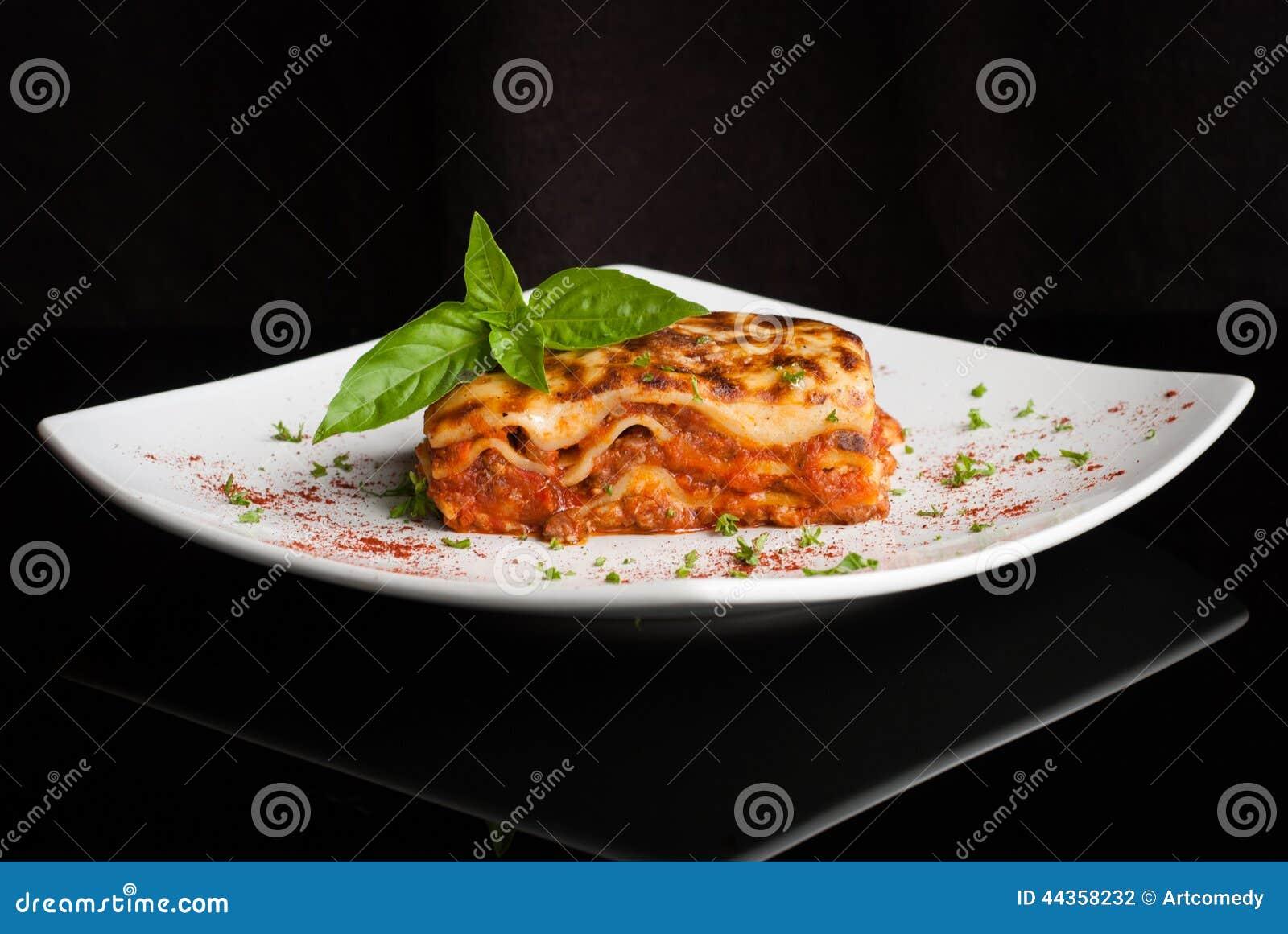 Lasagne al forno su un piatto bianco quadrato