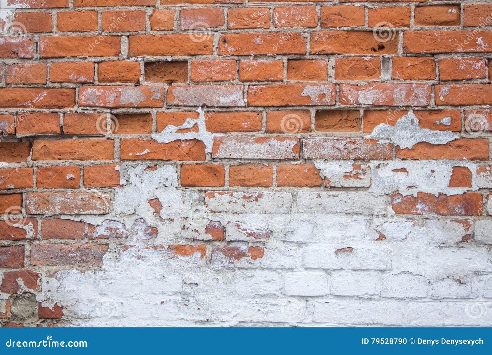 Lascado e descascando a pintura branca na parede de tijolo velha