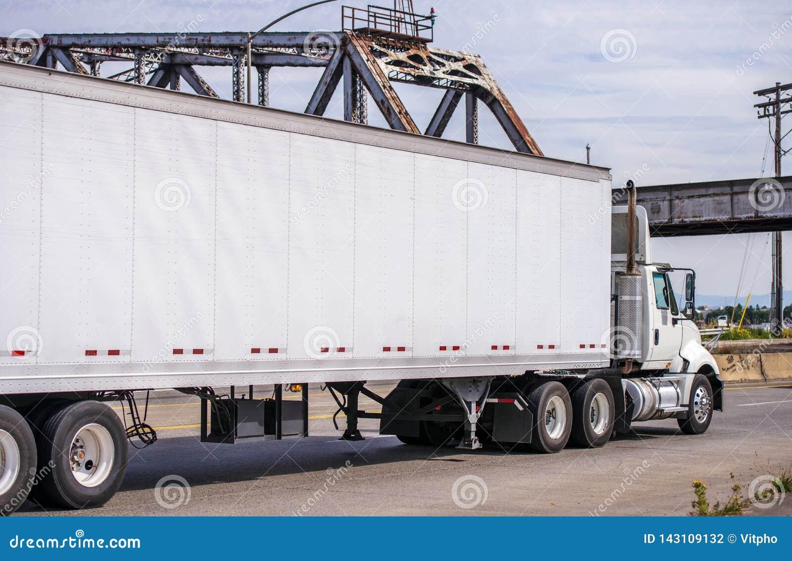 Lastbil för stor rigg för dagtaxi som halv transporterar kommersiellt gods i den halva släpet för torr skåpbil som kör på den lok