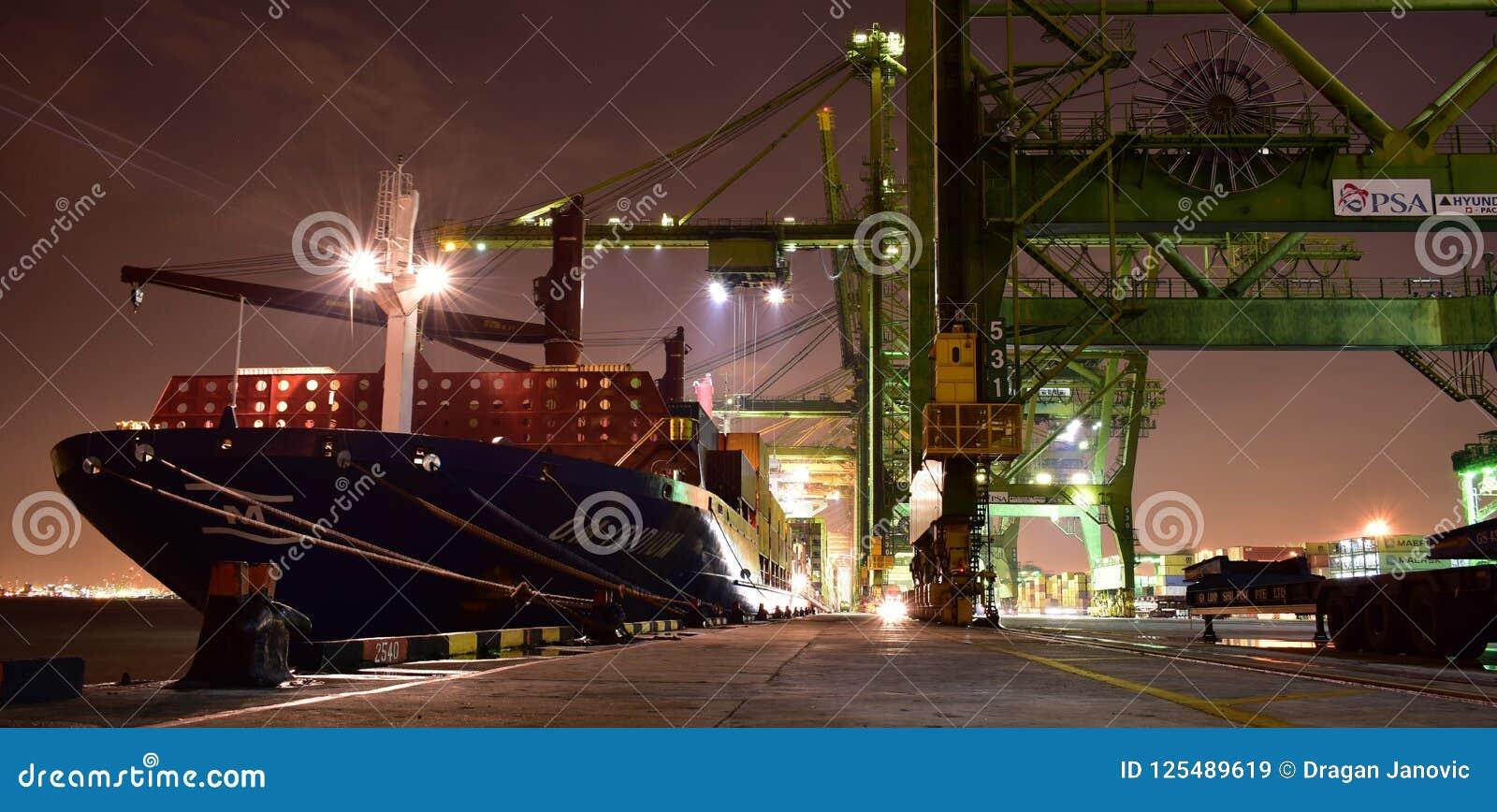 Lastoperationer på den upptagna behållareterminalen under natt