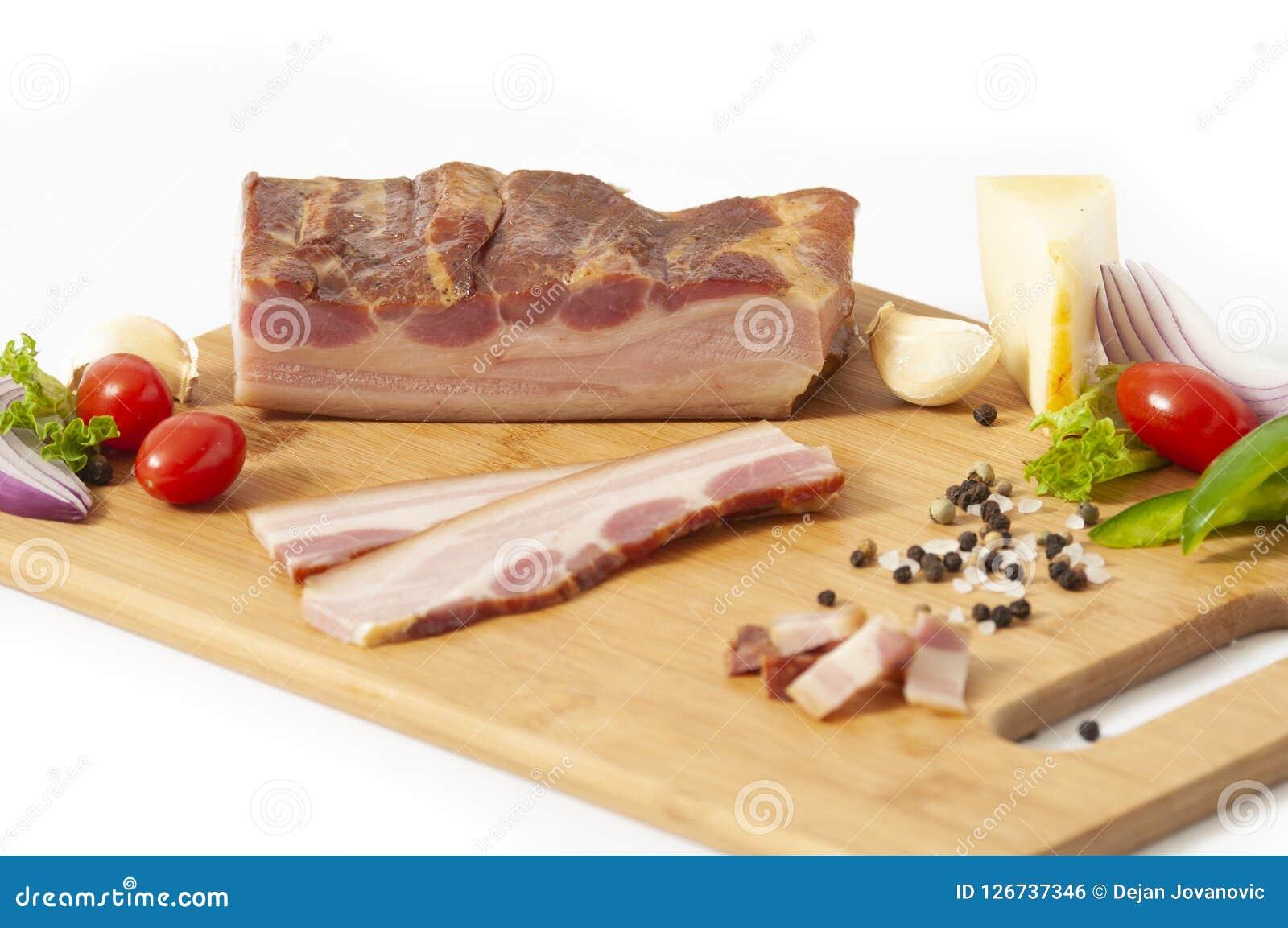 Lastra affumicata del bacon sul tagliere affettato con le verdure