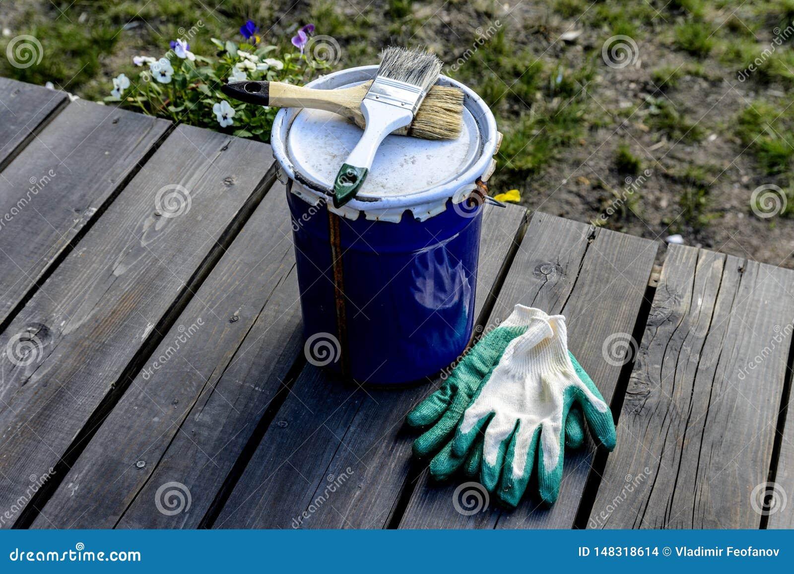 Lata da pintura que encontra-se no terra?o de uma casa privada com uma escova e as luvas, pronto para ser aberto e pintado reparo