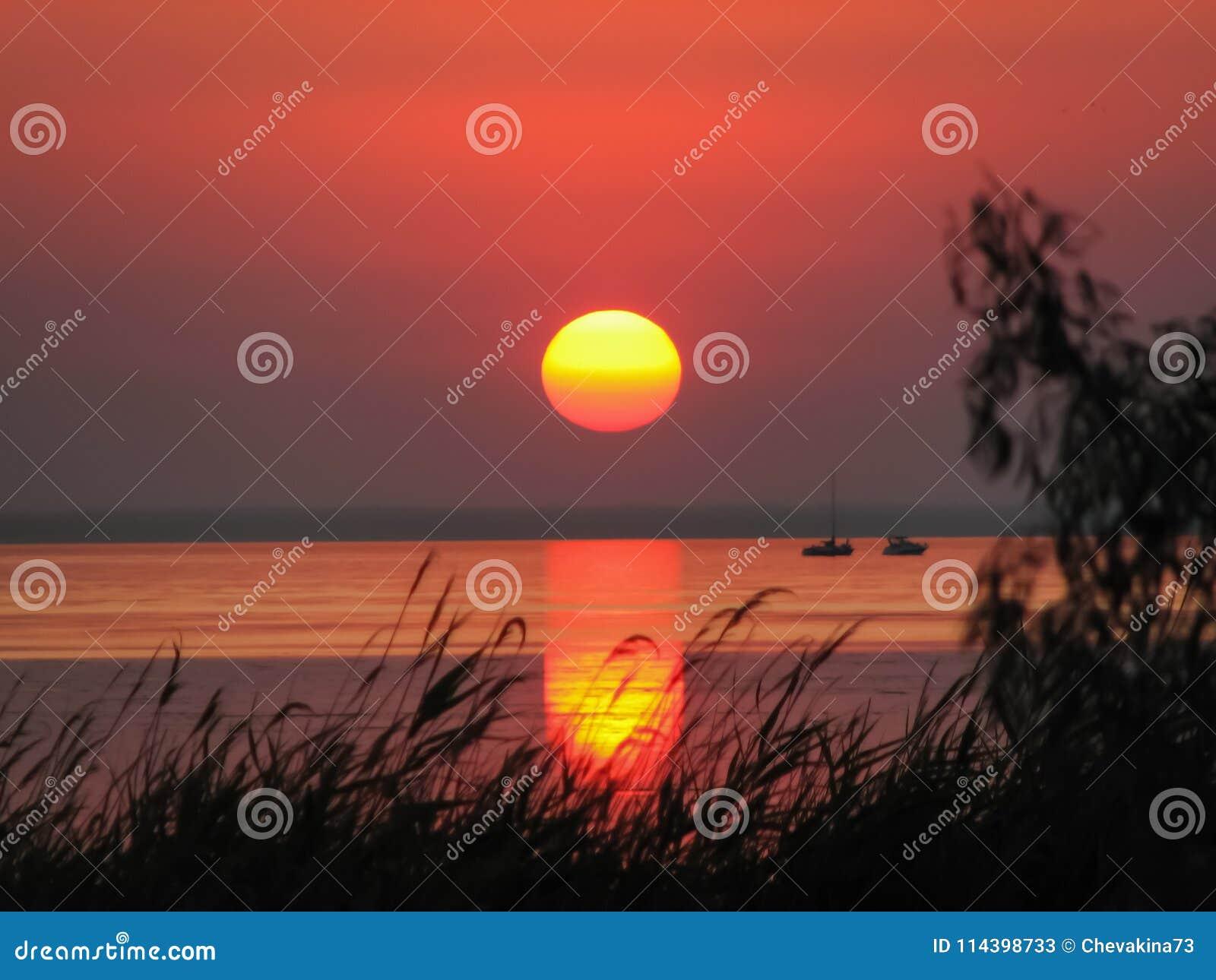 Lata no por do sol com as silhuetas do iate e do barco