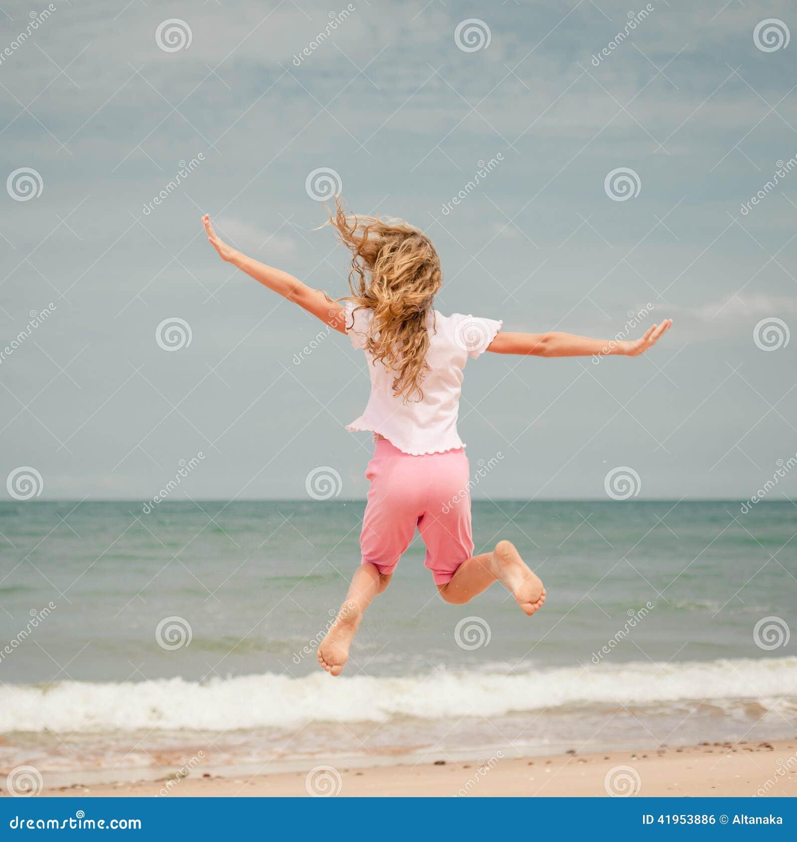 Latająca doskakiwanie plaży dziewczyna przy błękitnym dennym brzeg