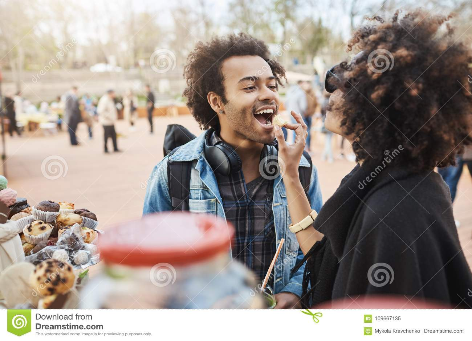Laterale vista delle coppie afroamericane sveglie nell amore divertendosi nel parco durante il festival dell alimento, contatore