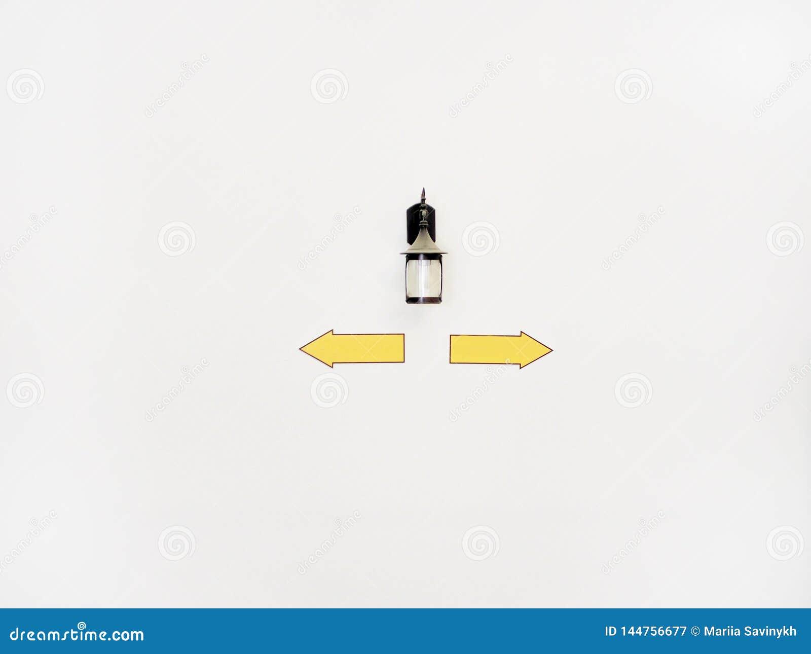 Laterne mit den Zeichen, die in verschiedene Richtungen auf die wei?e Wand mit copyspace zeigen