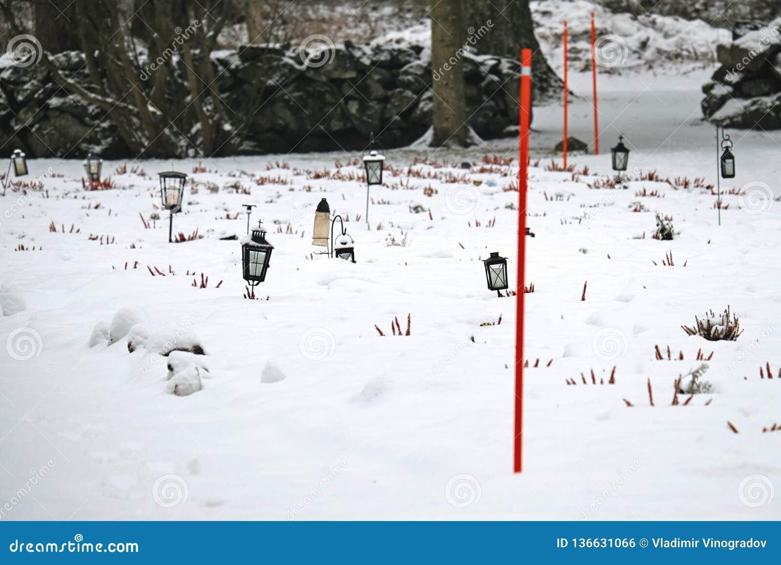 Laternen mit Kerzen am ernsten Yard des Kirchhofs umfasst mit Schnee im Winter