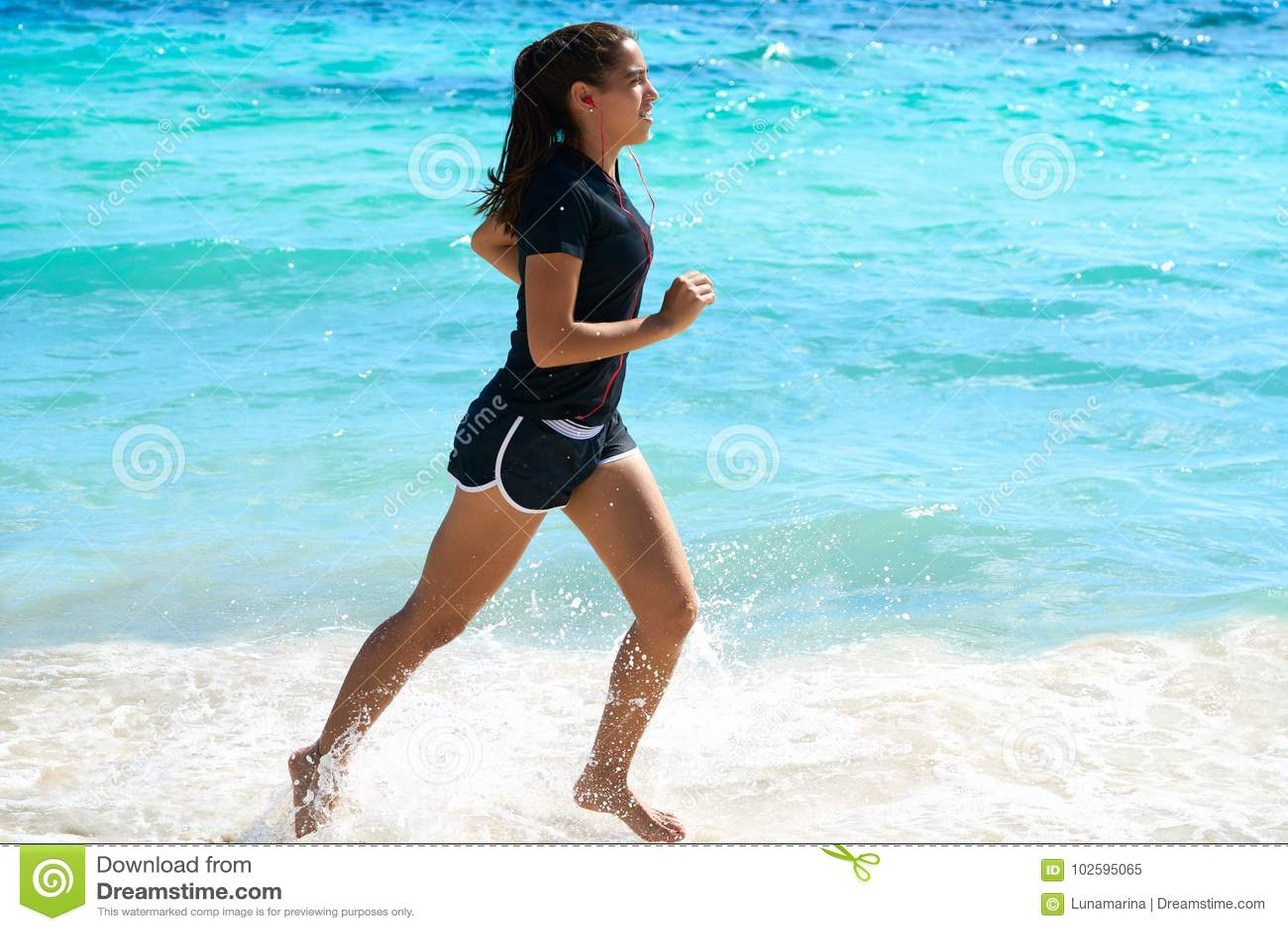 Latijns meisje die in Caraïbisch kuststrand lopen