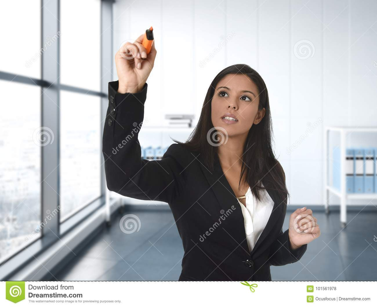 Latin business woman in formal suit writing with marker on invisible virtual screen or board at modern office