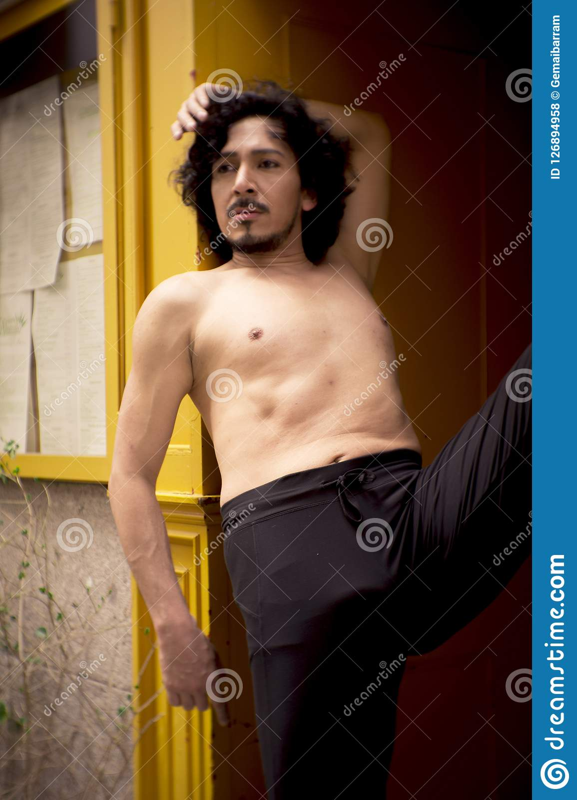 Latin male dancer posing with dancing figures