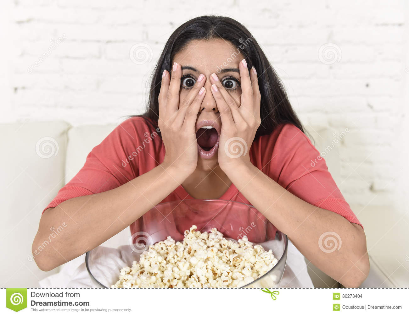 Latin woman sitting at home sofa couch in living room watching television scary horror movie