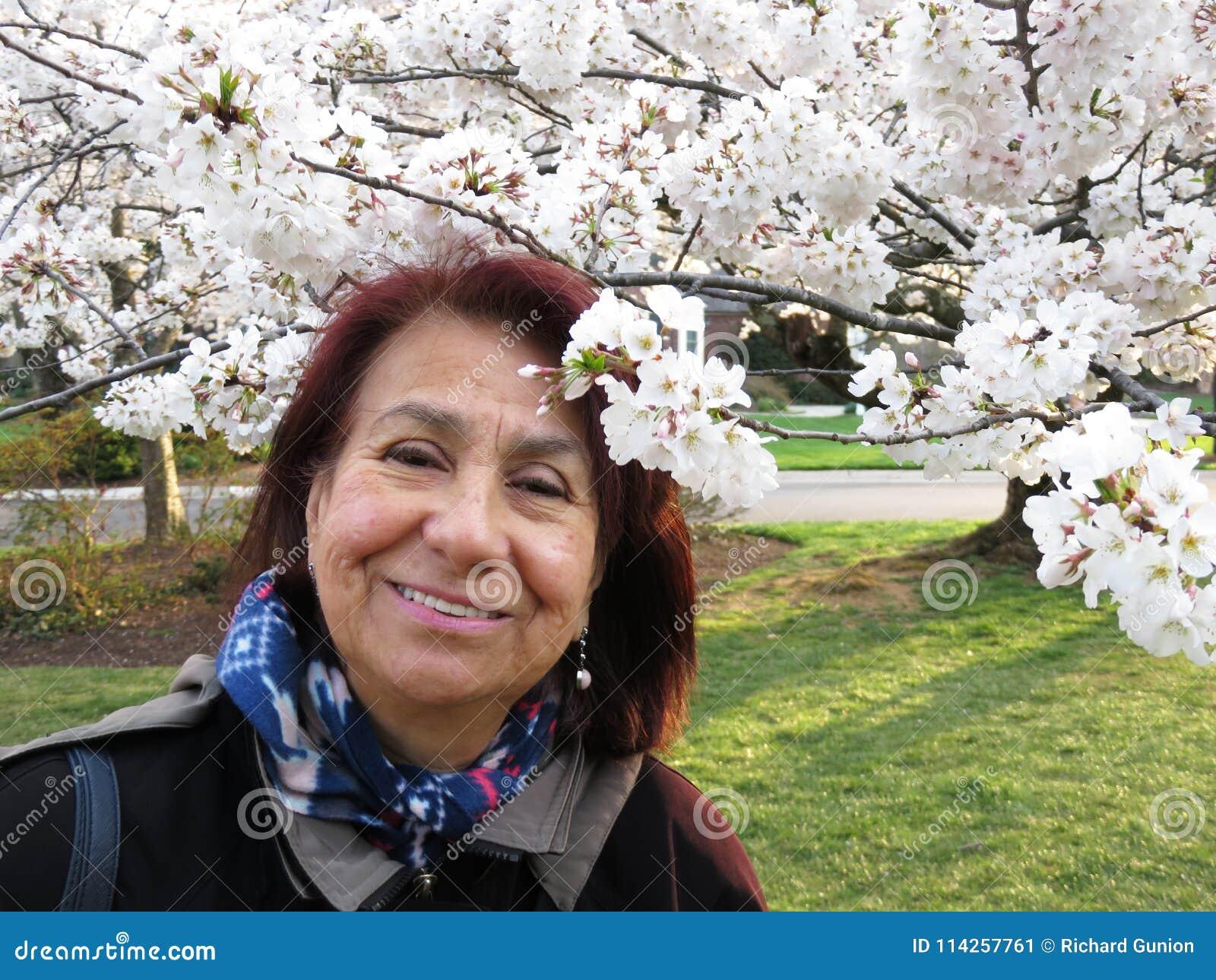 Latina-Frau, die Cherry Blossoms genießt