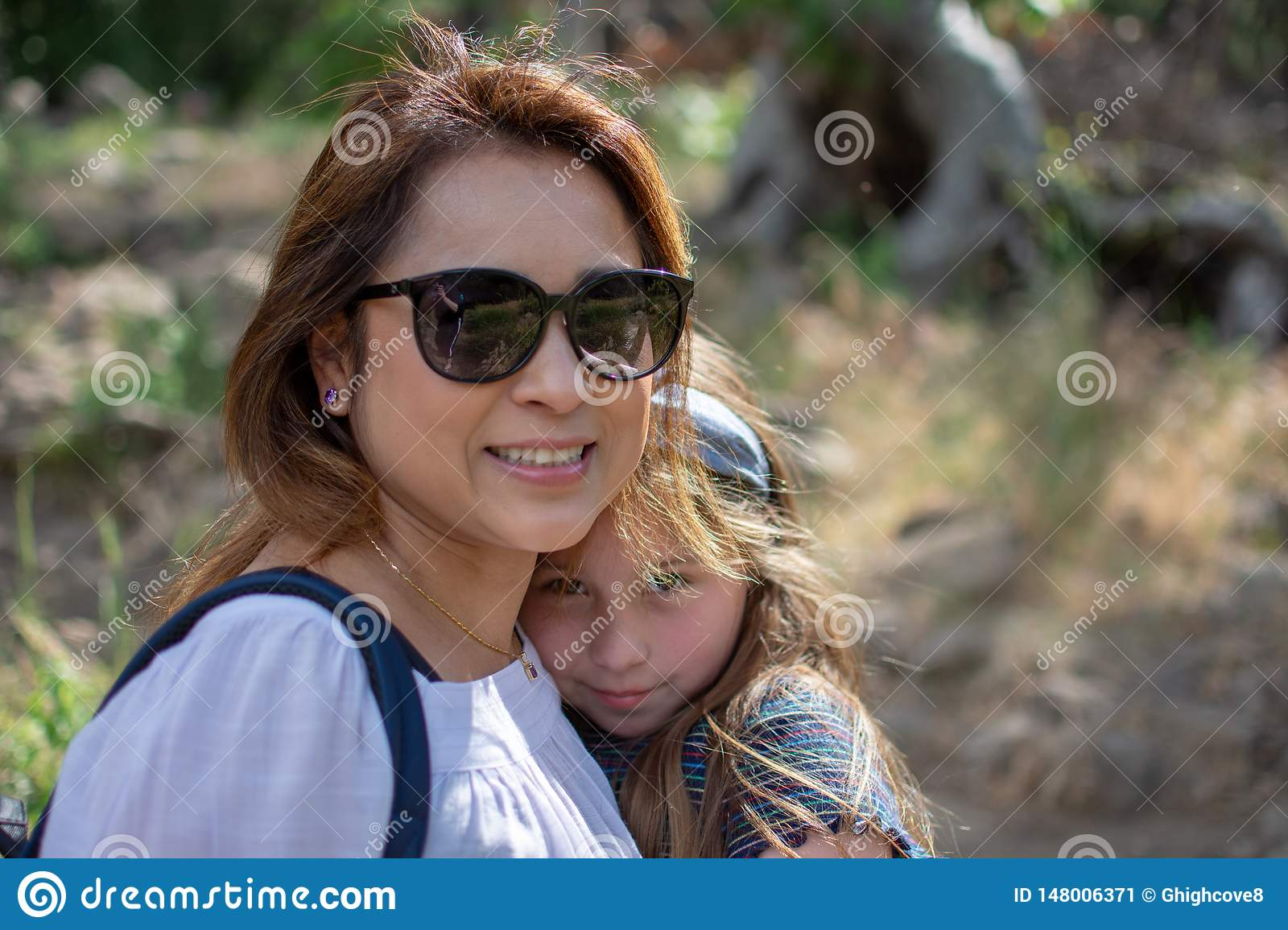 Latina Woman and daughter smiling together while standing in front of woods at a park