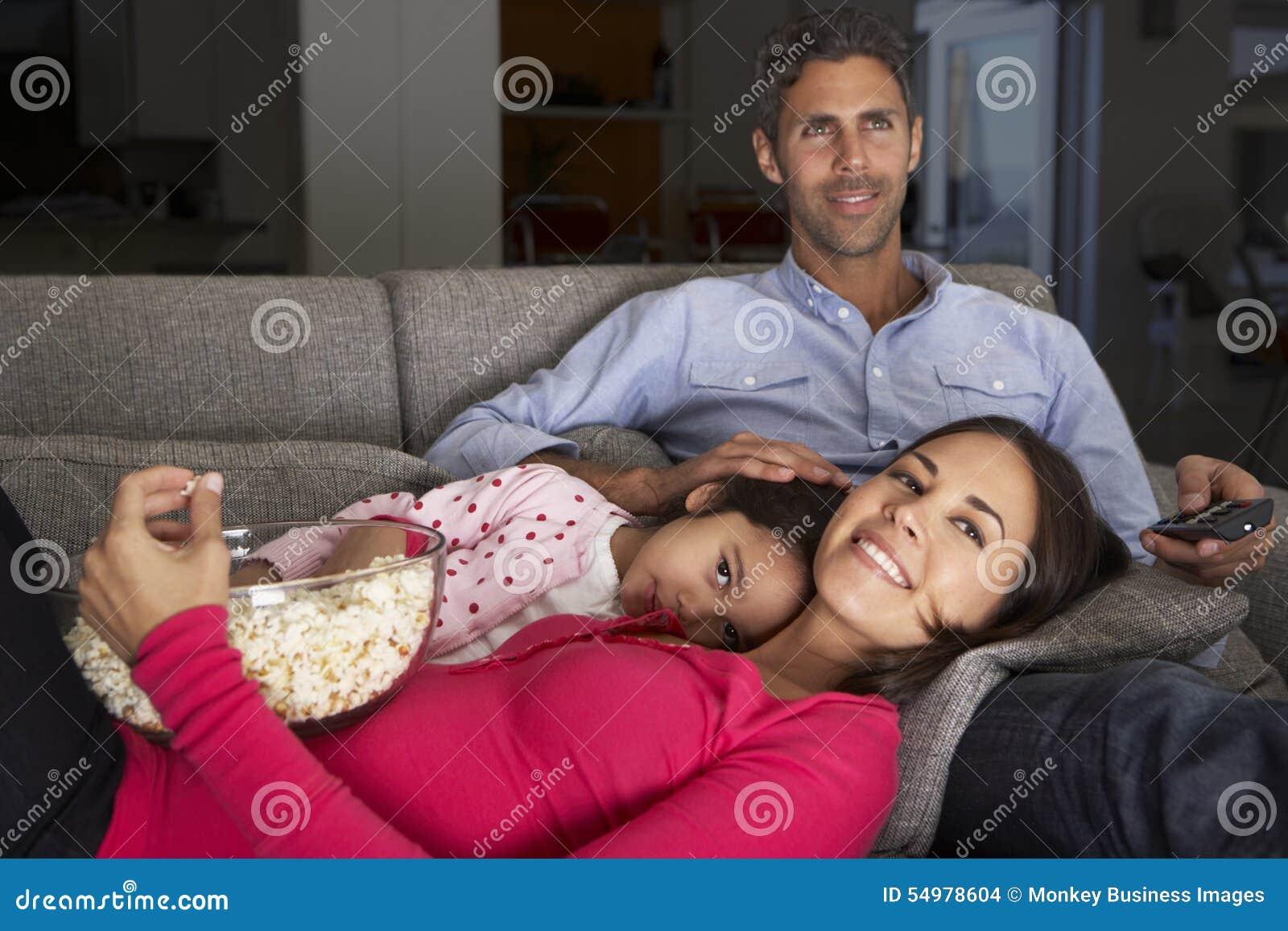 Latinamerikansk familj på Sofa Watching TV och ätapopcorn