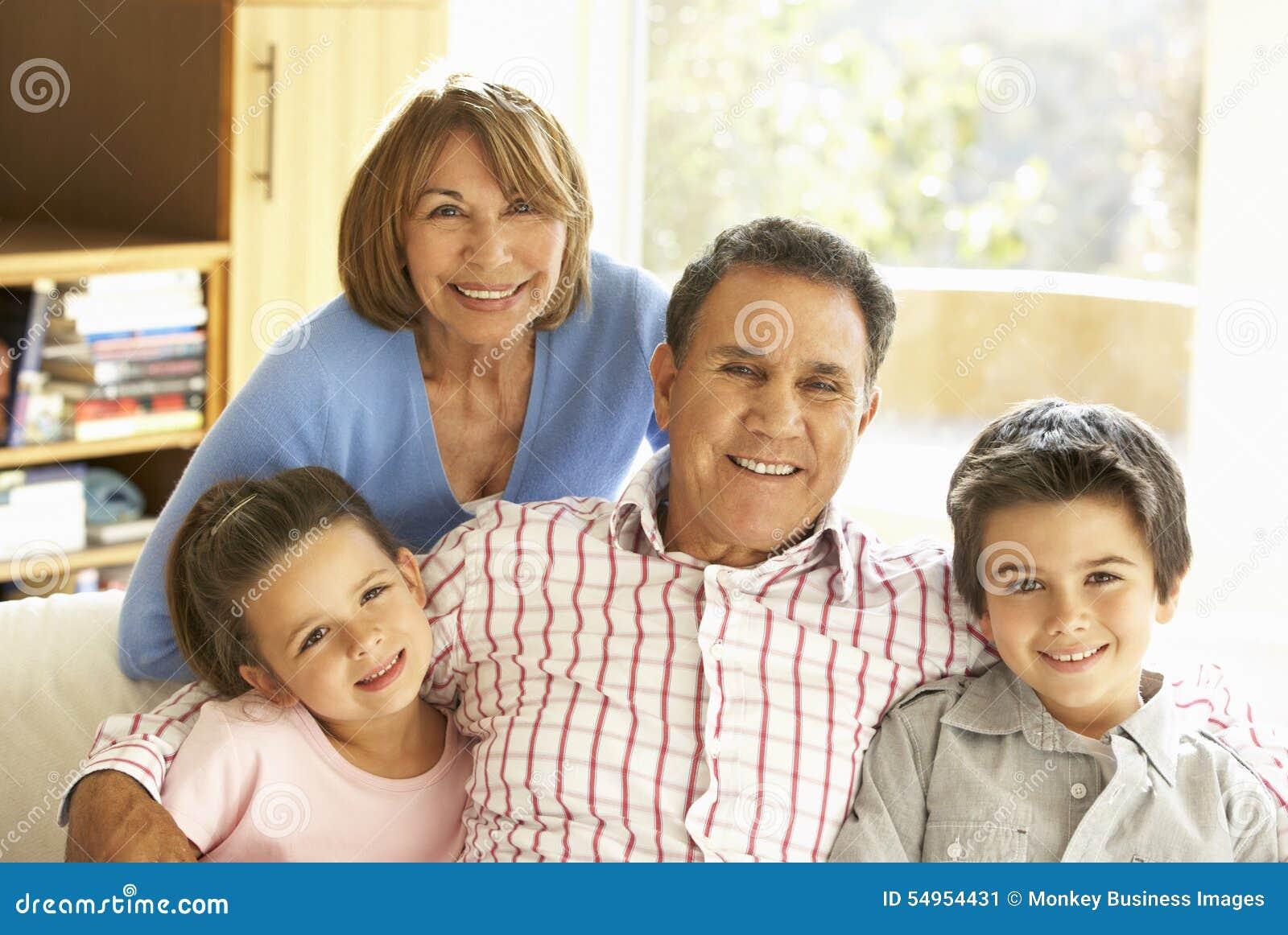 Latinamerikanska morföräldrar med barnbarn som kopplar av på Sofa At Hom