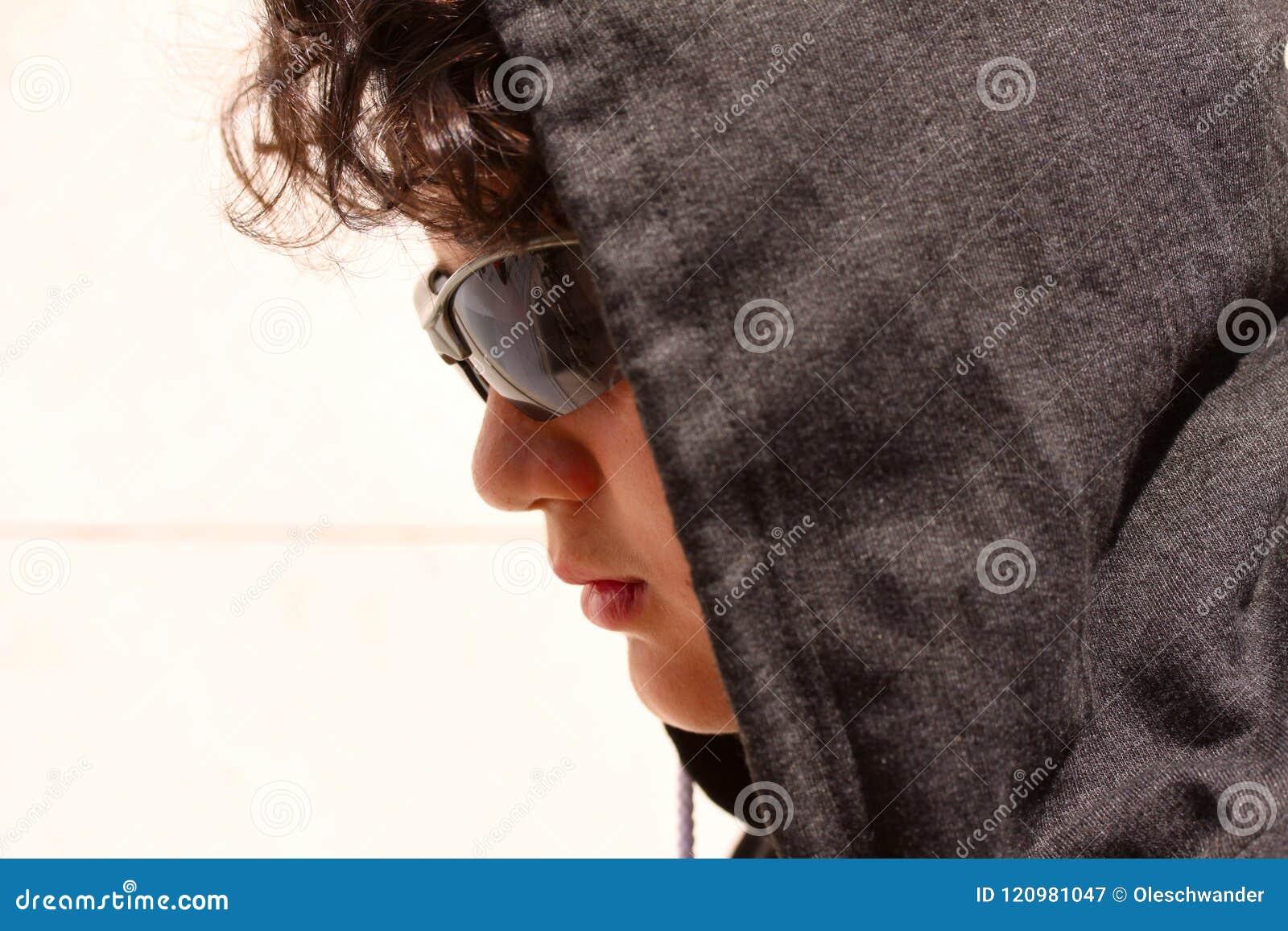 Latino-americano disturbato triste 13 anni dell adolescente che indossa una maglia con cappuccio e una posa scura degli occhiali