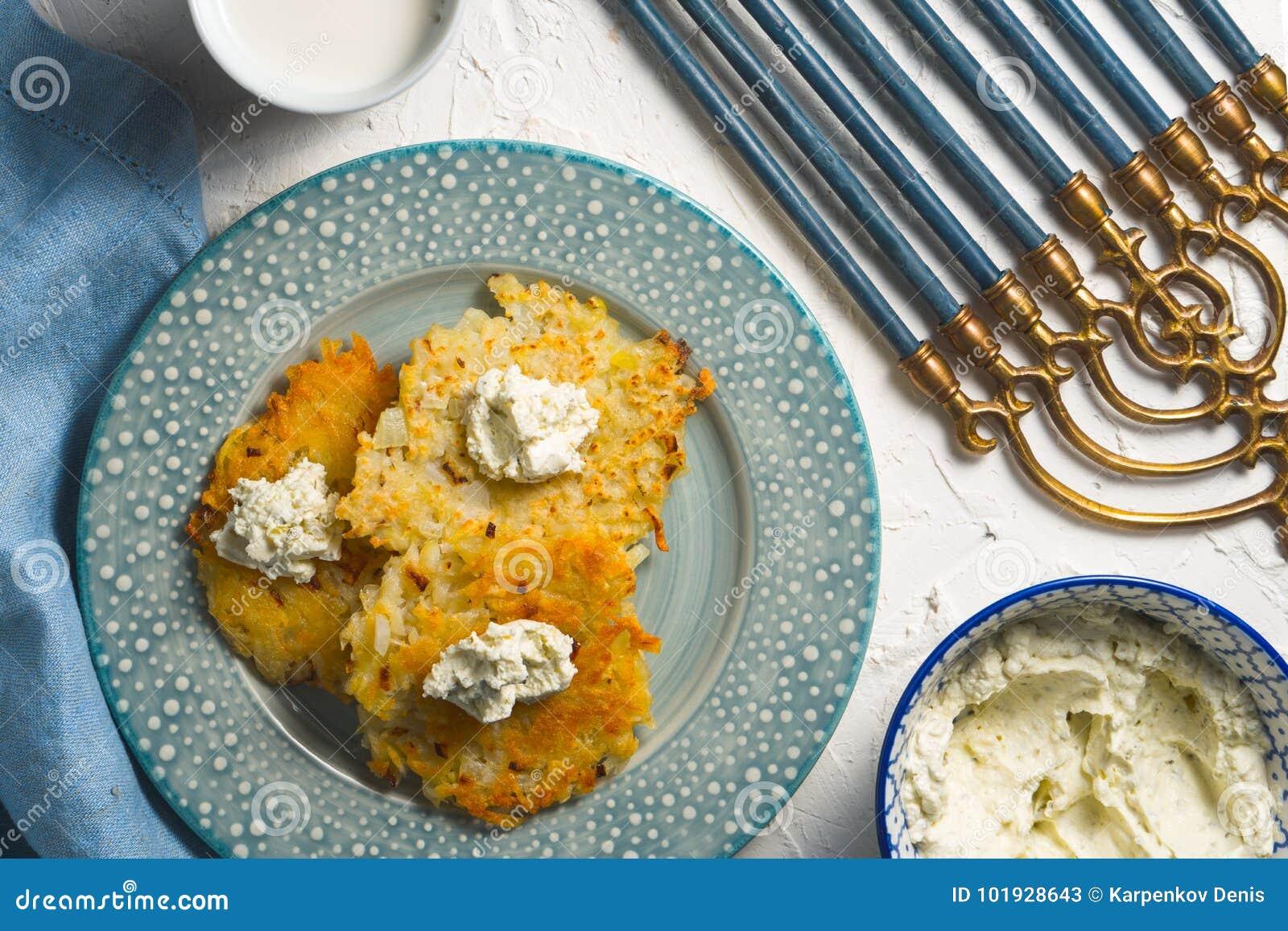 Latkes и сыр творога на плите и на голубой салфетке, chanukia