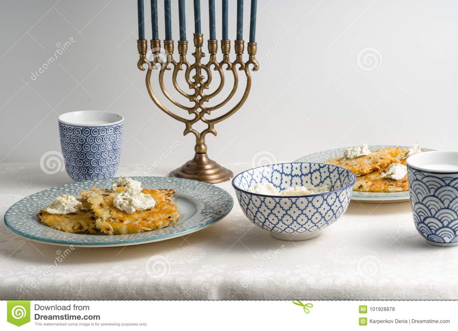 Latkes su un piatto, Chanukah, tazze con latte su una tovaglia bianca