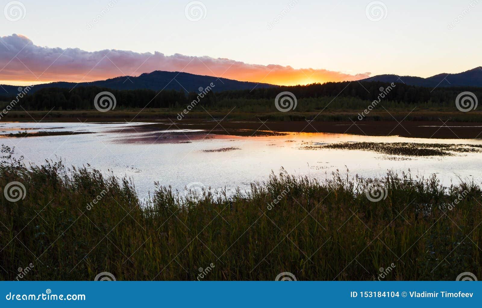 Lato krajobraz z rzecznym spływaniem między zielonymi wzgórzami na tle kolorowy zmierzchu niebo Ural region, Rosja