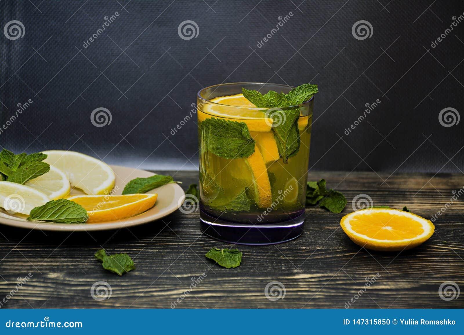 Lato, od?wie?aj?cy pomara?czowego nap?j z mennicy i pomara?cze plasterkami drewniany t?o zmrok Boczny widok