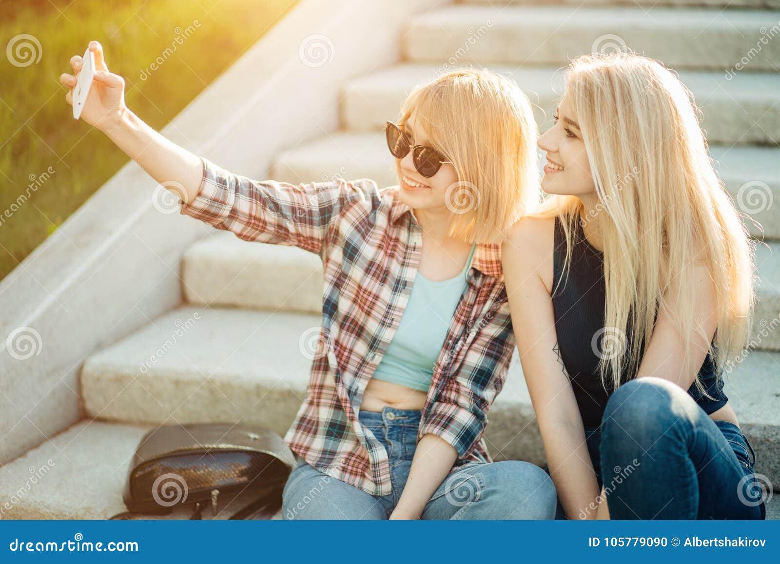 Lato plenerowy portret trzy przyjaciel zabawy dziewczyny bierze fotografie z smartphone