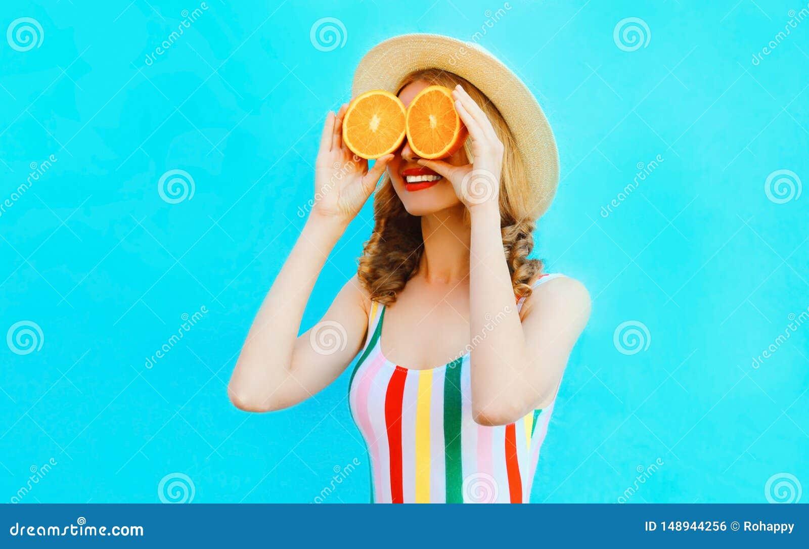Lato portreta kobiety szcz??liwy u?miechni?ty mienie w ona r?ki dwa plasterka chuje ona pomara?czowa owoc oczy w s?omianym kapelu