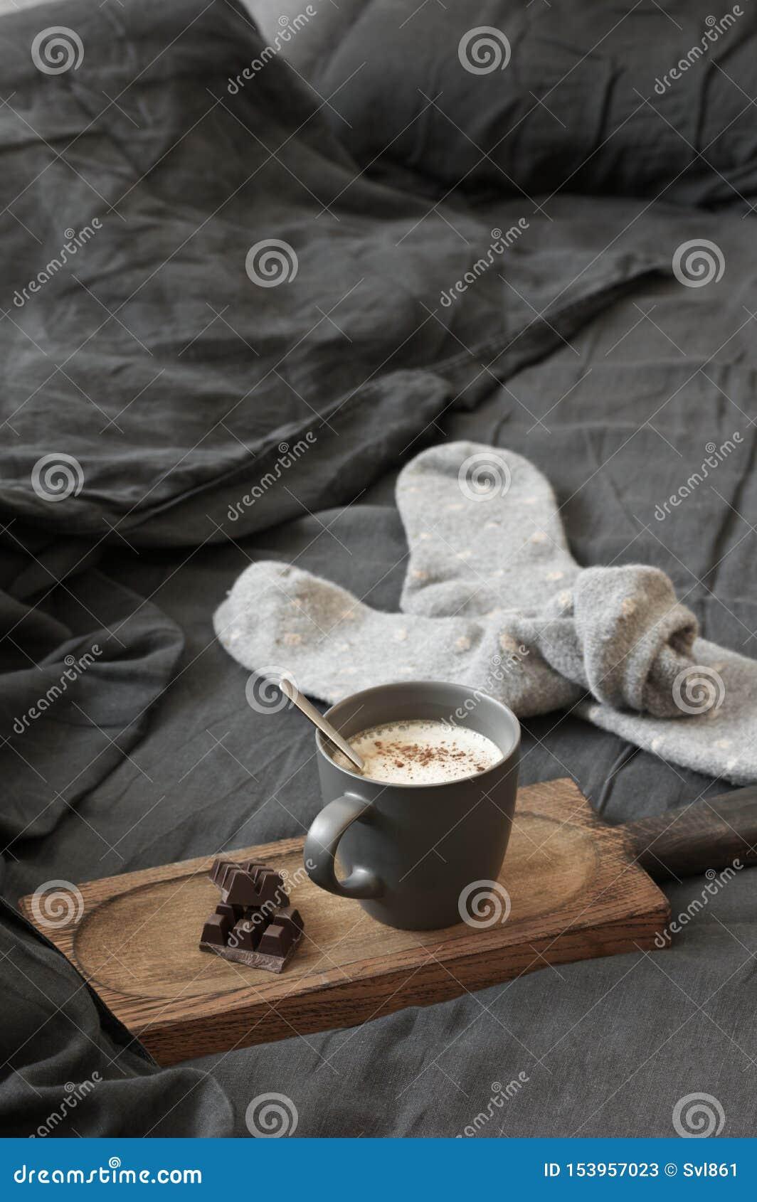 Latte кофе с шоколадом и шерстяные носки в отменятьой кровати