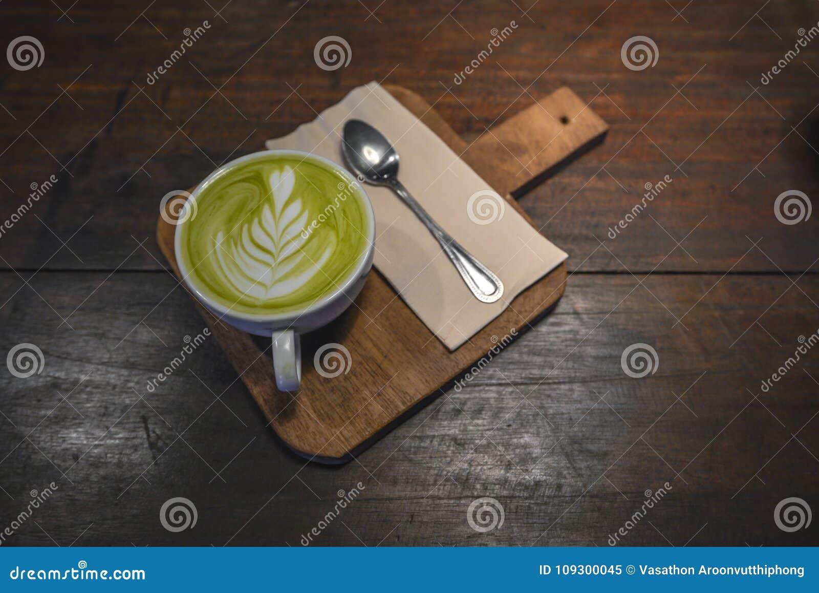 Latte caliente de Matcha en la taza blanca con la pequeña cuchara y servilleta en la tabla de madera