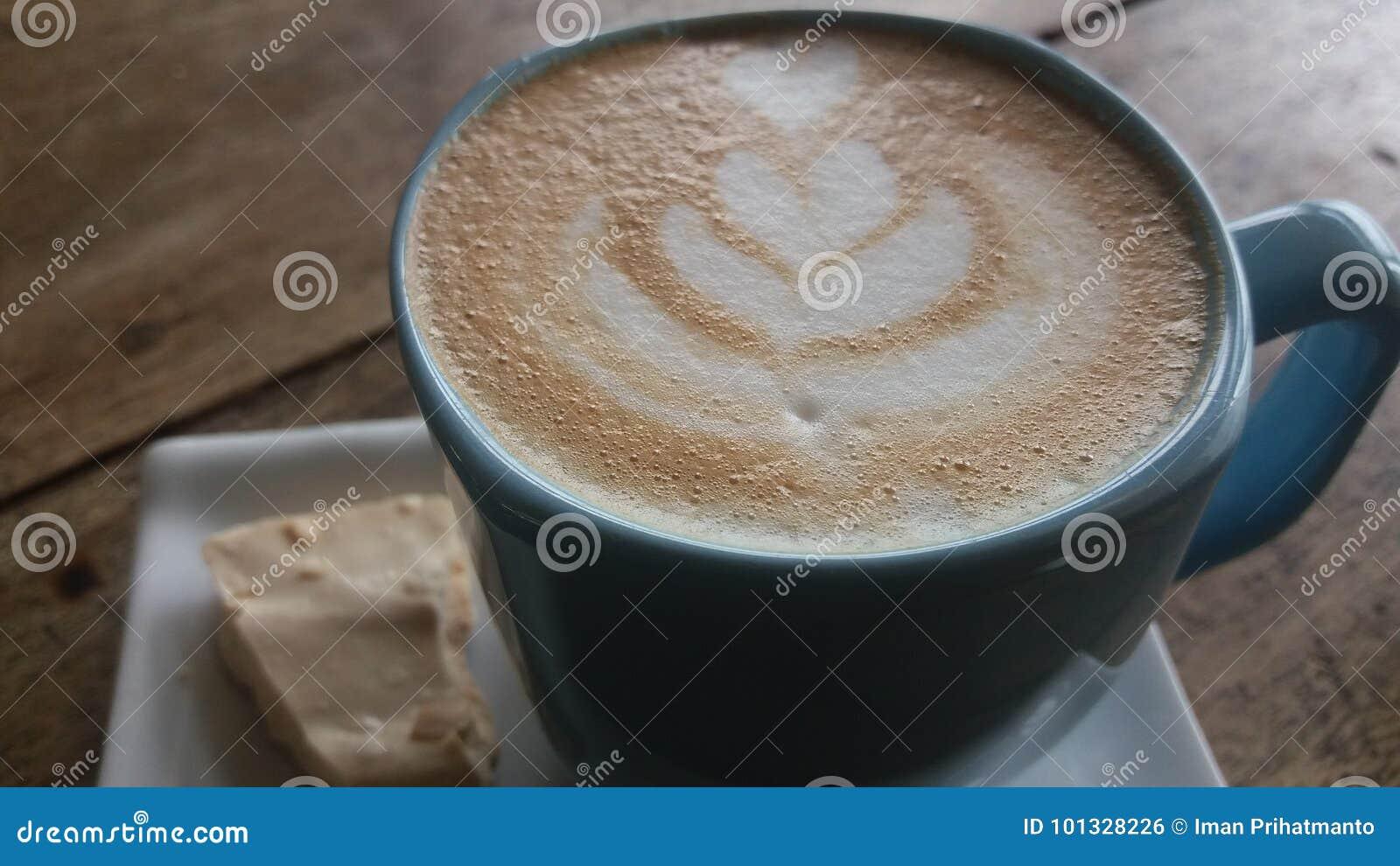 Latte del café en una taza con un pedazo de torta