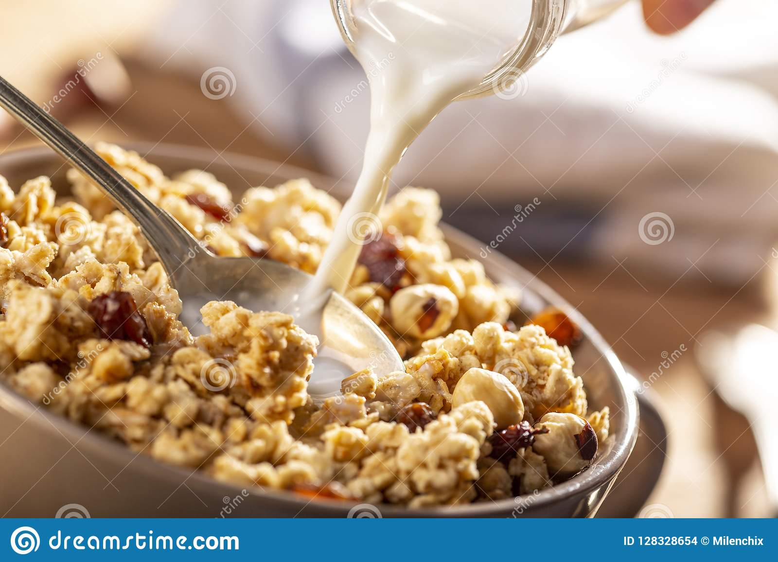 Latte di versamento in un arco del granola organico della nocciola