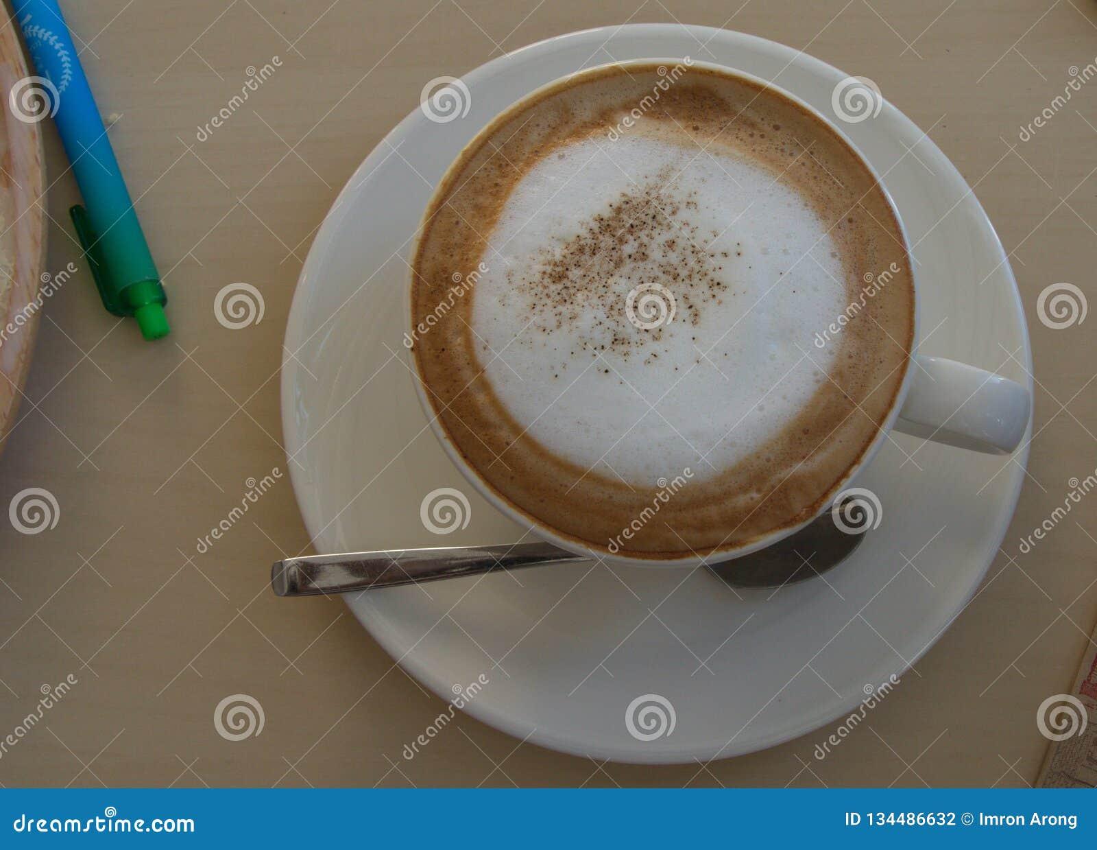 Latte en verre avec la vue supérieure de mousse et de cuillère