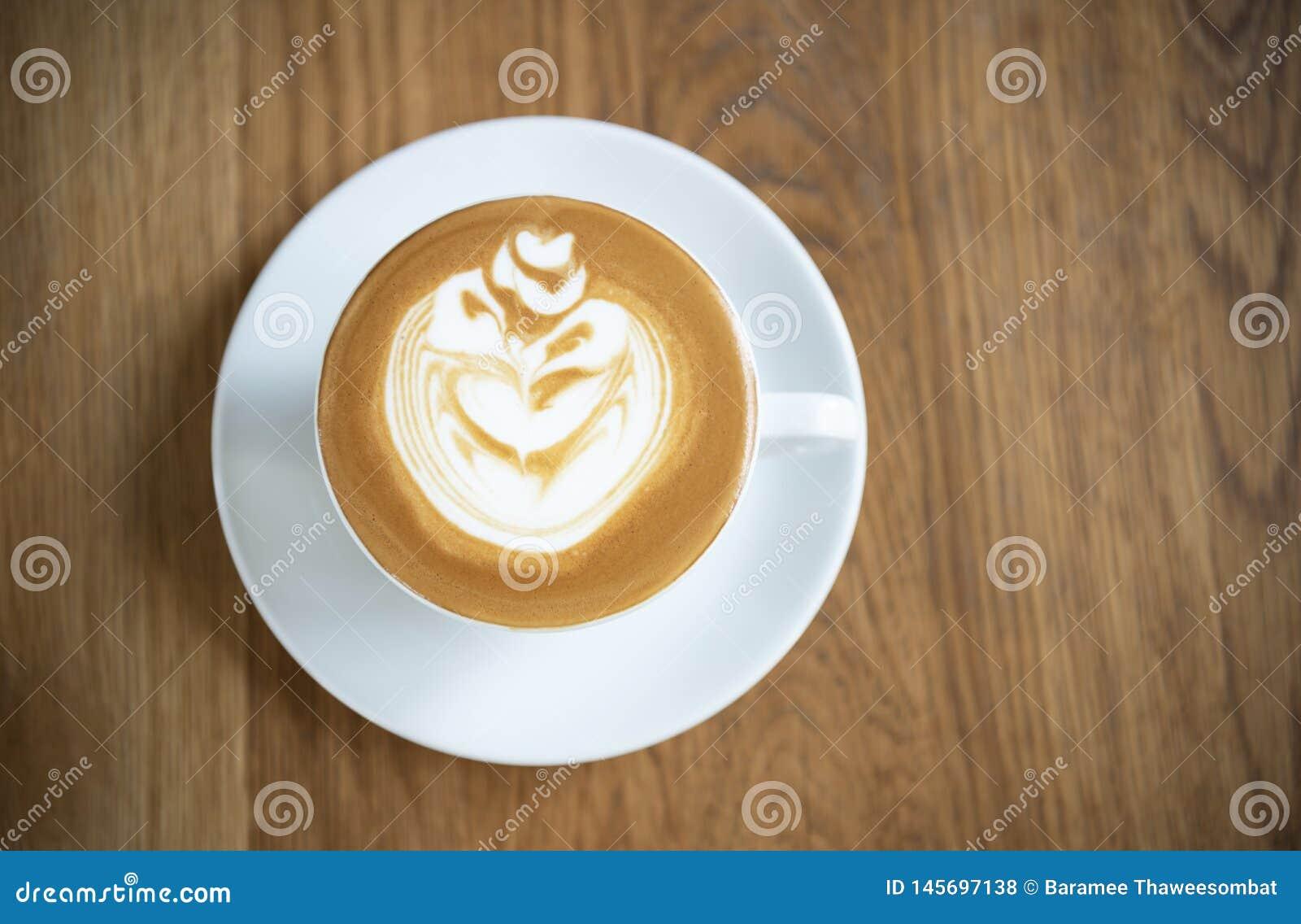 Latte ou cappuccino com espuma espumoso, opini?o superior de copo de caf? na tabela de madeira no caf?