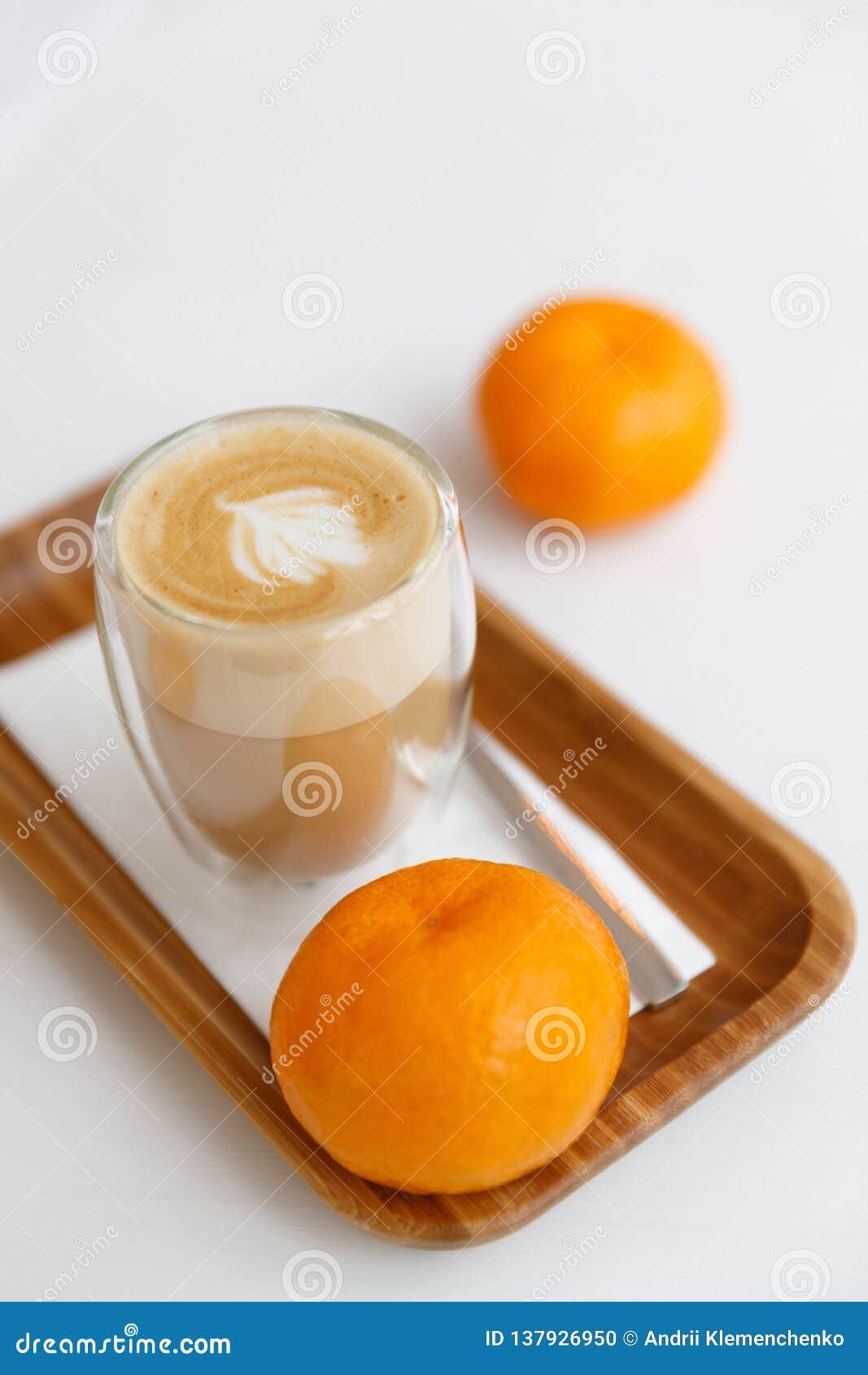 Latte su un vassoio di legno, sulle candele e sui mandarini Pausa caffè accogliente a casa