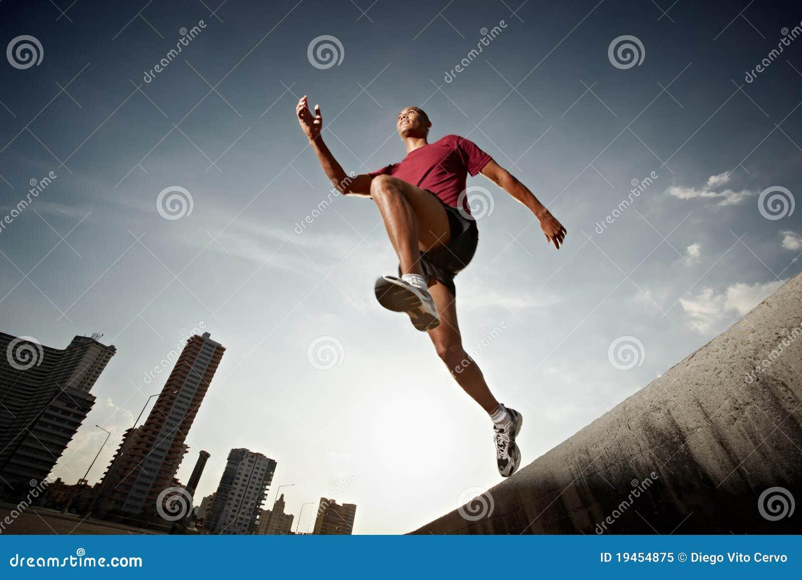 Latynoska doskakiwania mężczyzna bieg ściana