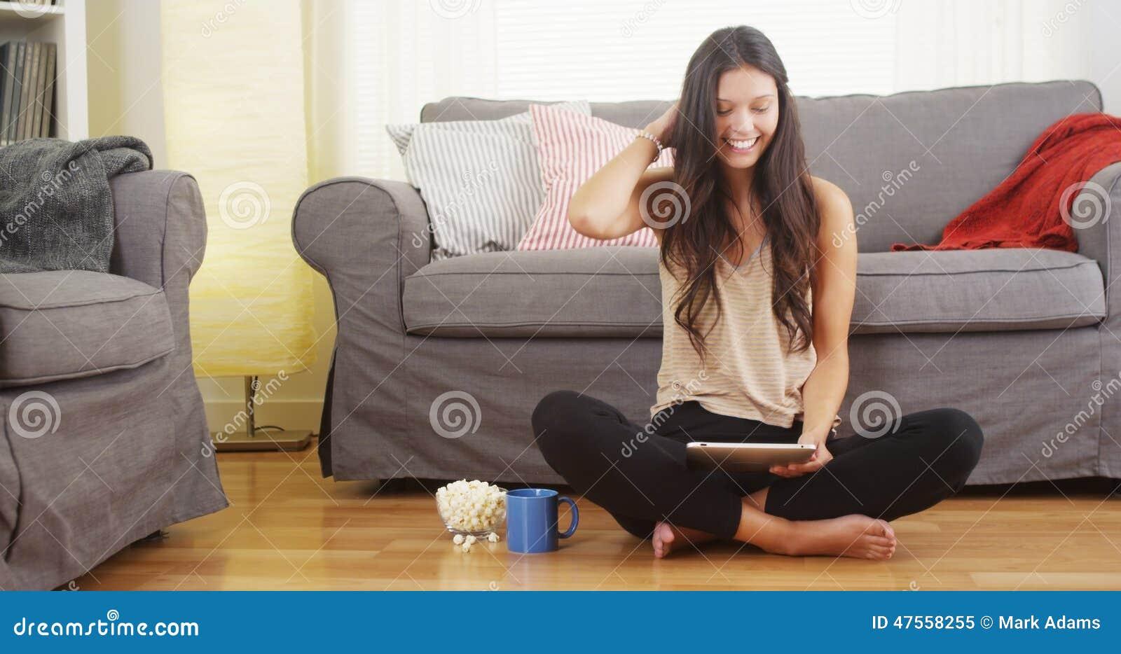 Latynoska kobieta uśmiecha się pastylkę i używa