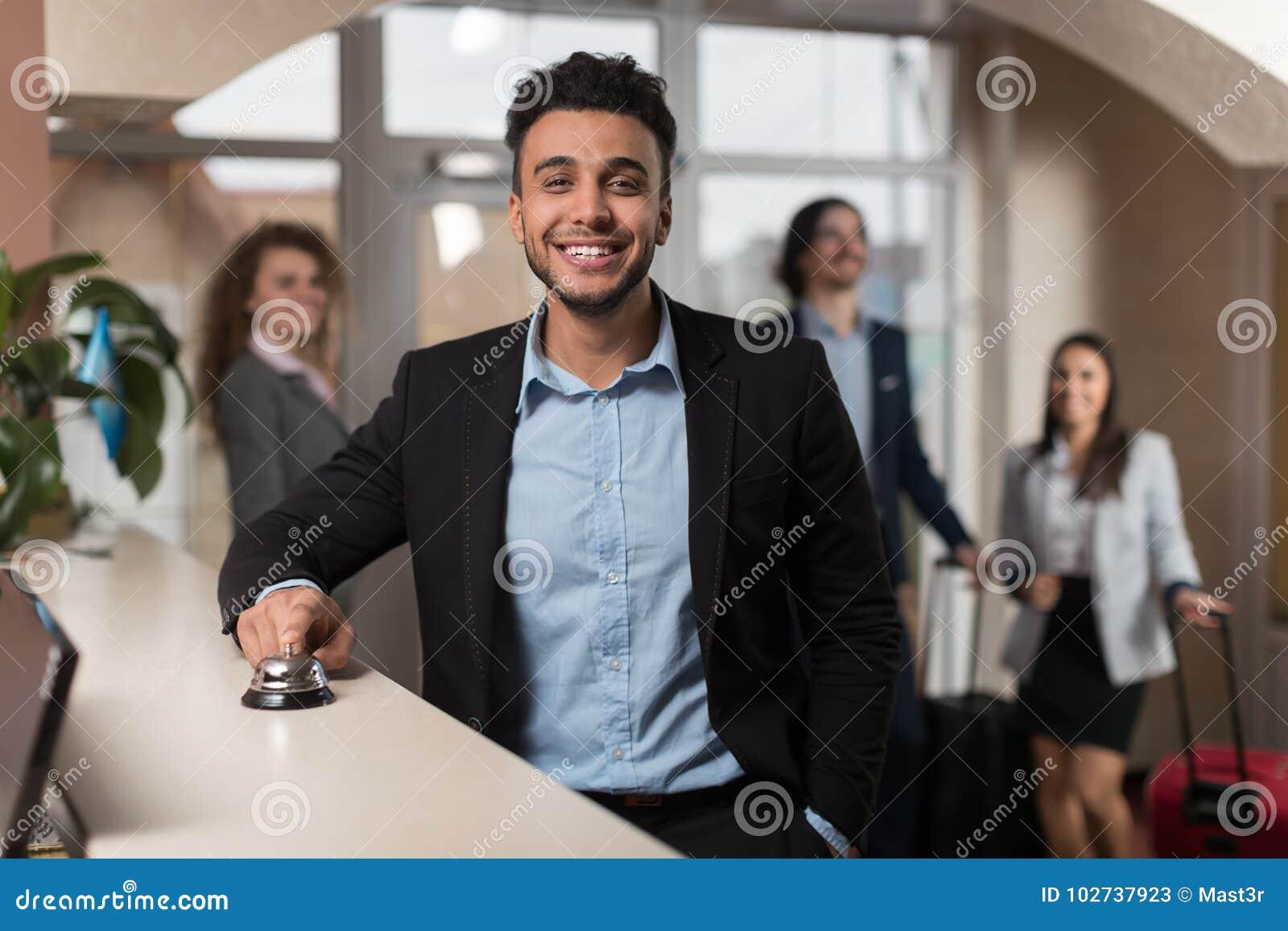 Latynoski Biznesowy mężczyzna Przyjeżdża Hotelowy czekanie Dla Sprawdza Wewnątrz Rejestracyjnych ludzi biznesu grupy W lobby