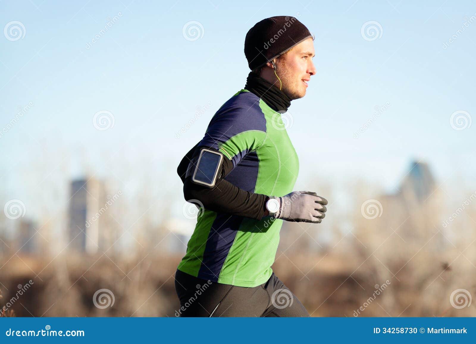 Laufender Mann, der im Herbst zur Musik am Telefon rüttelt