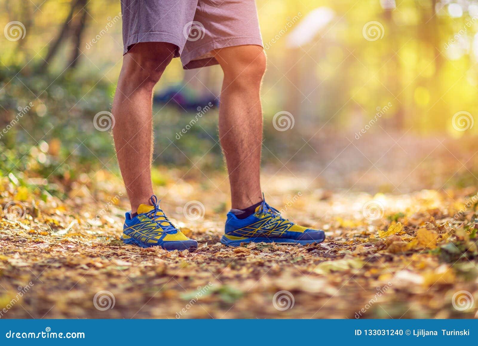 Laufender Sporteignungsmann Schließen Sie oben von den männlichen Beinen und von den Schuhen Mann