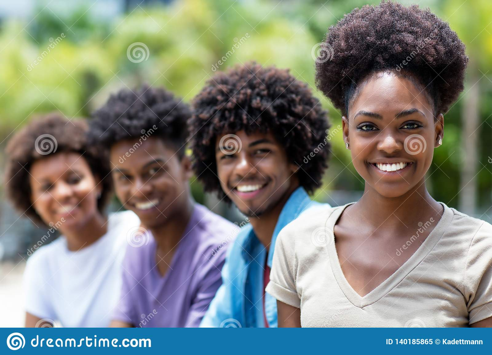 Laughing african american woman with group of young adults in line