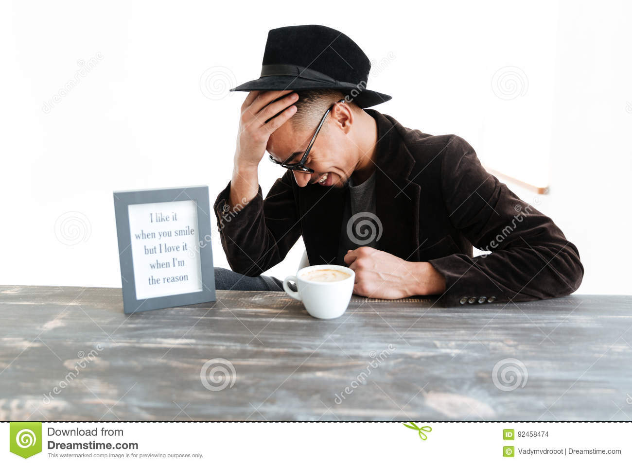 Laughing African Man Sitting By The Table Stock Photo