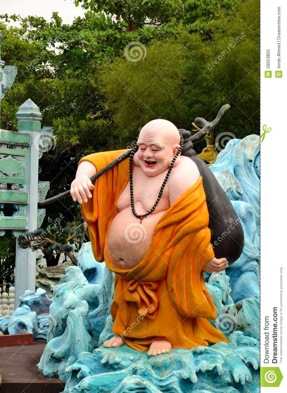 saffron robed fat laughing Buddhist monk carrying stick and satchel ...