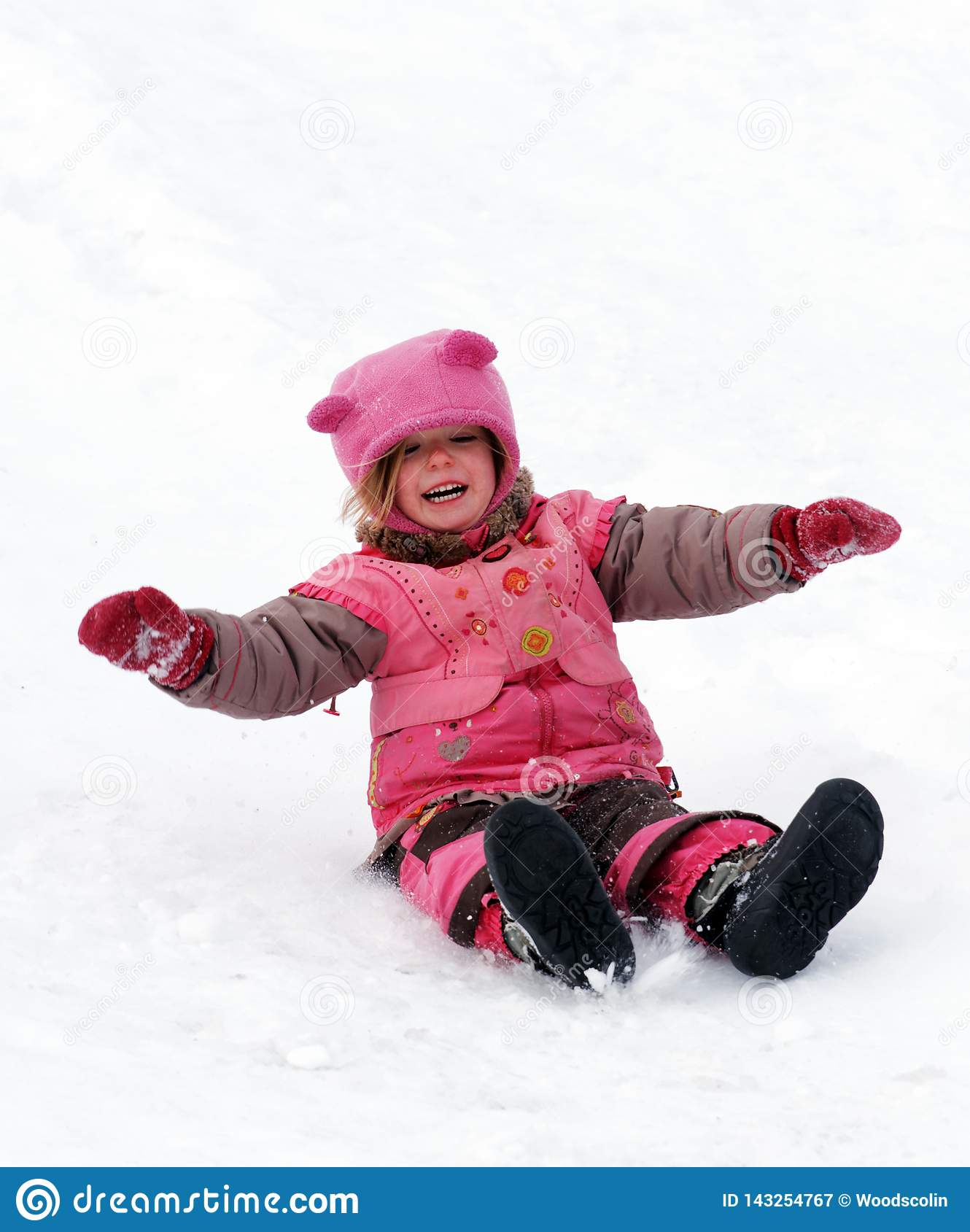 A laughing child sliding in the snow