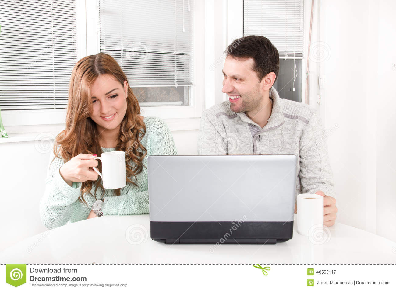 Laughing couple browsing the internet at the laptop